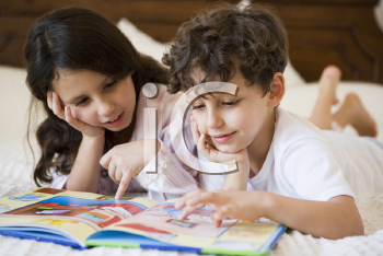 Royalty Free Photo of Two Children Reading at Bedtime