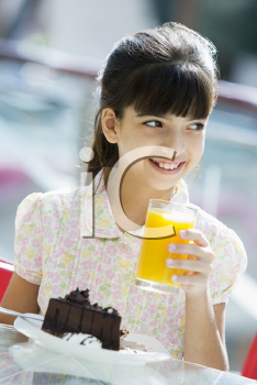 Royalty Free Photo of a Girl Having Juice and Cake