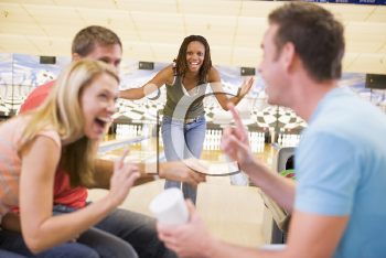 Royalty Free Photo of a Woman Bowling With Friends