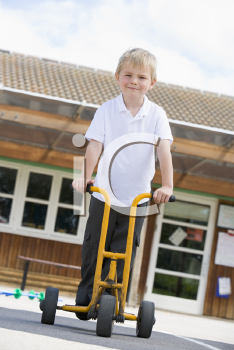 Royalty Free Photo of a Child Outside a School on a Scooter
