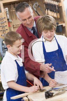 Royalty Free Photo of a Teacher and Two Boys in Woodworking