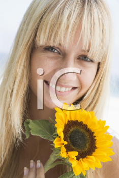 Royalty Free Photo of a Woman Holding a Sunflower