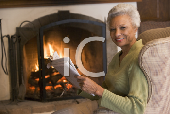 Royalty Free Photo of a Woman Reading Beside a Fireplace