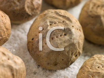 Royalty Free Photo of Jacket Potatoes Baked on a Tray of Sea Salt