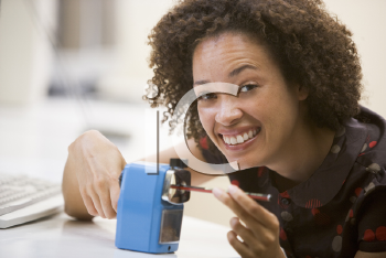 Royalty Free Photo of a Woman Using a Pencil Sharpener