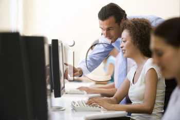 Royalty Free Photo of a Man Helping a Woman at a Computer