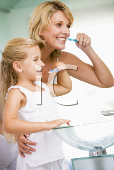 Royalty Free Photo of a Woman and Girl Brushing Their Teeth