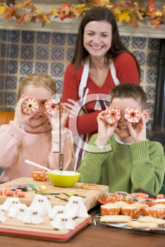 Royalty Free Photo of a Mother and Two Children With Halloween Treats
