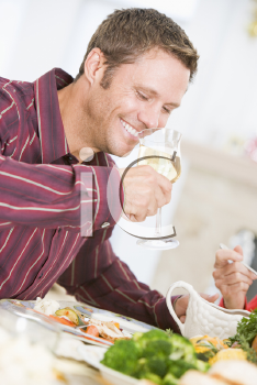 Royalty Free Photo of a Man Drinking Wine With Dinner