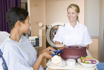 Royalty Free Photo of a Nurse Serving a Meal to a Patient