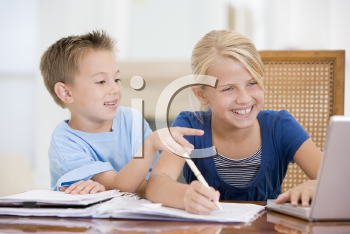 Royalty Free Photo of a Girl Doing Homework and Her Brother Pointing at the Laptop