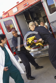 Royalty Free Photo of Paramedics and a Doctor Unloading a Patient