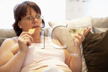 Royalty Free Photo of a Woman With Chips and Wine on the Sofa