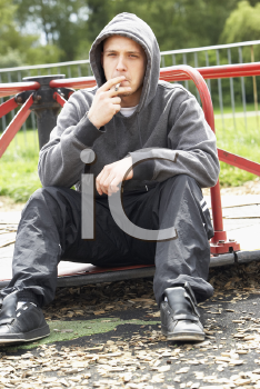 Royalty Free Photo of a Guy Smoking a Joint in a Playground