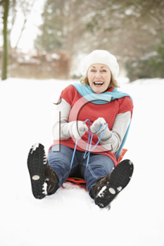 Senior Woman Sledging Through Snowy Woodland