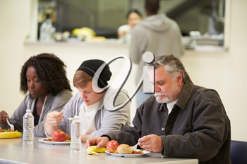 People Sitting At Table Eating Food In Homeless Shelter