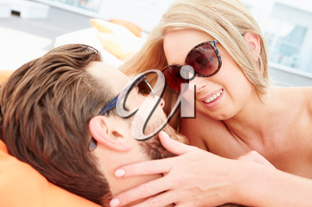 Young Couple On Holiday Relaxing By Swimming Pool