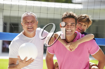Male Multi Generation Family Playing Volleyball In Garden