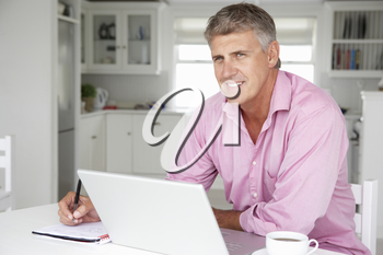 Mid age man working on laptop at home