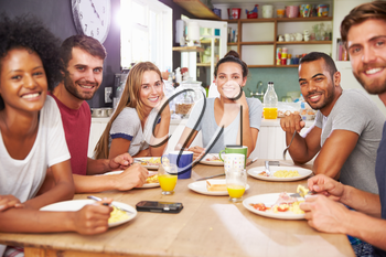 Group Of Friends Enjoying Breakfast In Kitchen Together
