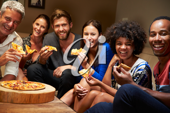 Group of adult friends eating pizza at a house party