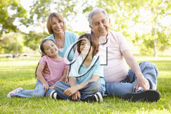 Hispanic Grandmother And Grandfather Relaxing With Grandchildren In Park