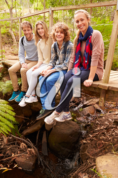 Portrait of family sitting on a bridge in a forest, vertical