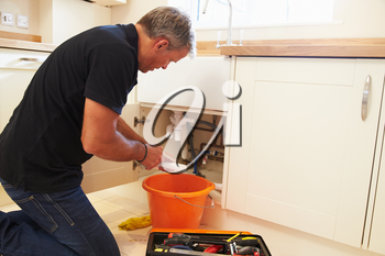 Male plumber preparing a pipe for the sink in a kitchen