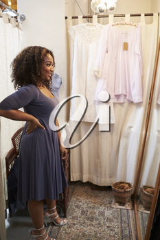 Smiling woman trying on dress in changing room, vertical