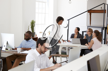 Woman briefing colleagues around a desk in open plan office