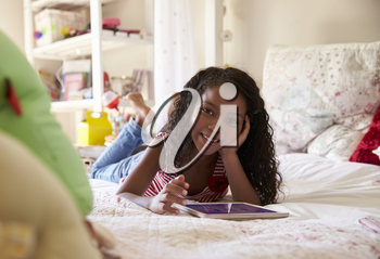 Portrait Of Young Girl Lying On Bed Using Digital Tablet