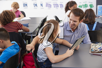 Teacher and schoolgirl with tablet computer looking at each other