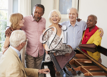 Group Of Seniors Standing By Piano And Singing Together
