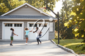 Mother And Children Playing Basketball On Driveway At Home