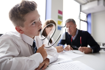 Concentrating Male High School Student Wearing Uniform Working At Table With Teacher Talking To Pupils In Background