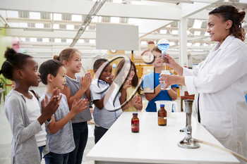 Lab technician showing excited kids a science experiment