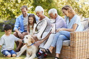 Three generation family petting a dog in the garden