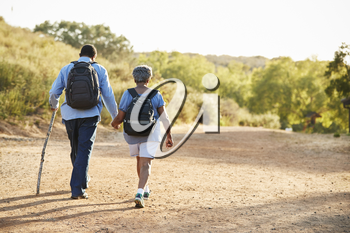 Rear View Of Senior Couple Wearing Backpacks Hiking In Countryside Together