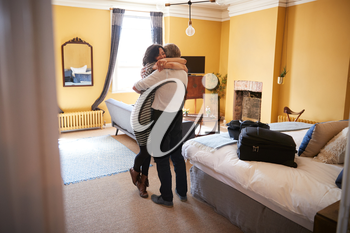 Mature couple embracing in hotel room, back view full length