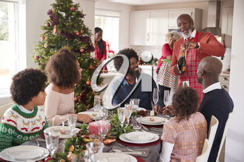 Black grandfather opening champagne for his multi generation family, gathered in the dining room for Christmas dinner