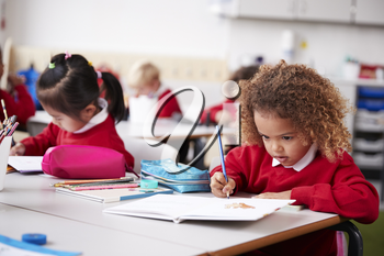 Young schoolgirl wearing school uniform sitting at a desk in an infant school classroom drawing, close up
