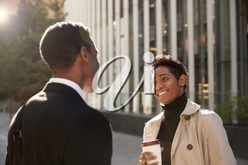 Smiling young black businesswoman standing on the street with a takeaway coffee, talking to her male colleague, selective focus