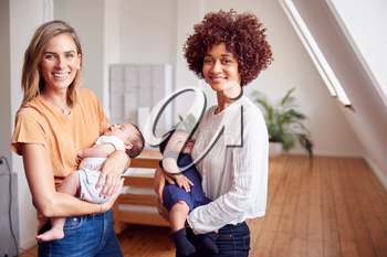 Portrait Of Two Mothers Meeting Holding Newborn Babies At Home In Loft Apartment