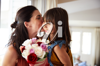 Mid adult woman kissing her daughter, who's given her a bunch of flowers on her birthday, close up