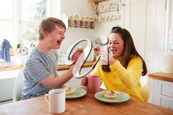 Young Downs Syndrome Couple Enjoying Tea And Cake In Kitchen At Home