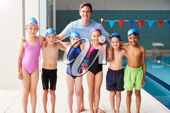 Portrait Of Male Coach With Children In Swimming Class Standing Edge Of Indoor Pool