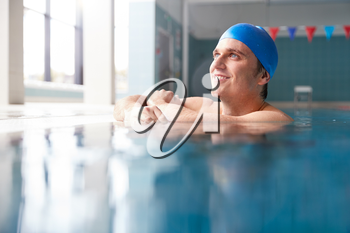 Male Swimmer Wearing Hat And Goggles Training In Swimming Pool