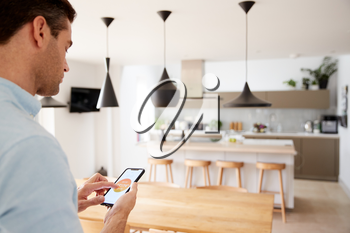 Man Using App On Smart Phone To Control Central Heating Temperature In House