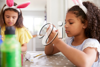 Two Girls Wearing Bunny Ears Sitting At Table Decorating Eggs For Easter At Home