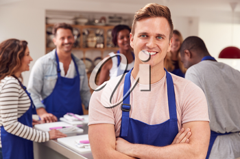 Portrait Of Smiling Man Wearing Apron Taking Part In Cookery Class In Kitchen